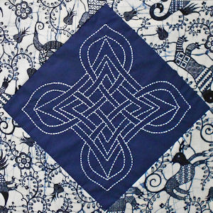 Navy blue fabric with white stitching, set with Dutch Wax batik triangles.