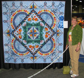 Sharon at Des Moines, standing with her quilt.